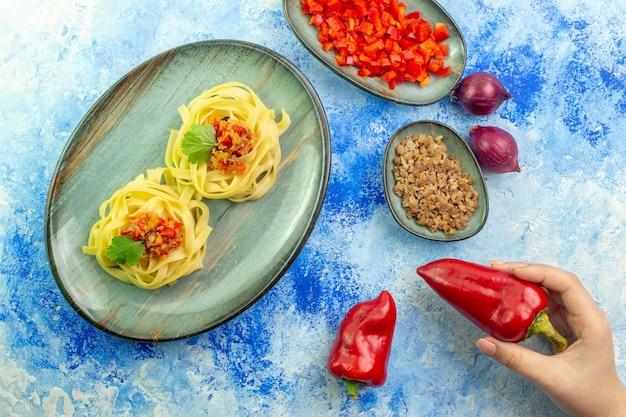 青いテーブルにおいしいパスタと必要な野菜の肉と青いプレートの上面図