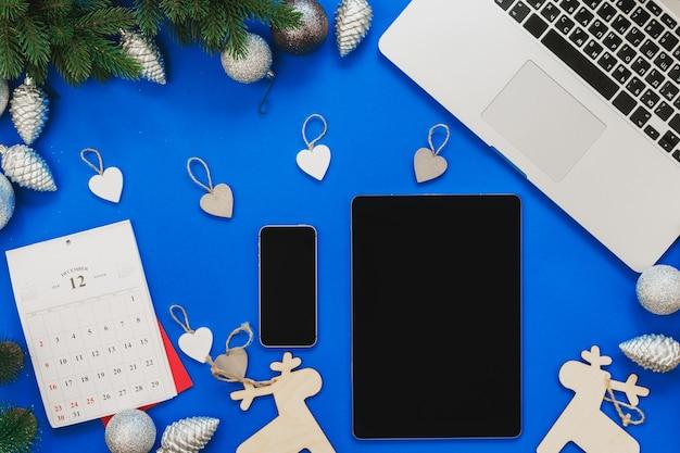 노트북과 크리스마스 장식이 있는 파란색 테이블의 상위 뷰