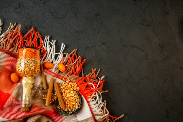 Вид сверху бутылки с сырыми зернами кукурузы и бобов кумкватами и палочкой корицы на плед с кисточкой с копией пространства на черном