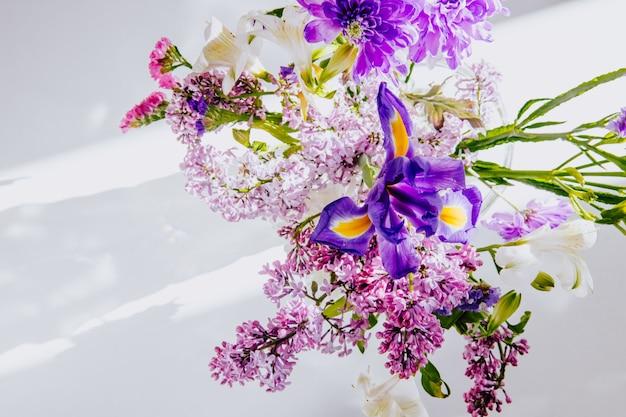 Вид сверху на букет цветов сирени с альстромерией белого цвета темно-фиолетового ириса и статицы в стеклянной вазе на белом фоне