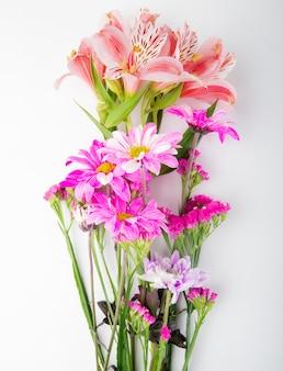 Вид сверху на букет розовых хризантем с цветами статицы и альстромерии на белом фоне