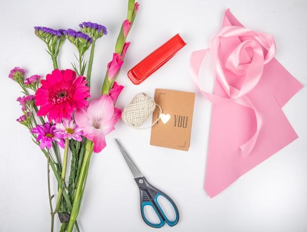 白い背景の上のスターチスとピンク色のガーベラとグラジオラスの花とピンクのリボンはさみと小さなポストカードと赤いホッチキスの花束のトップビュー