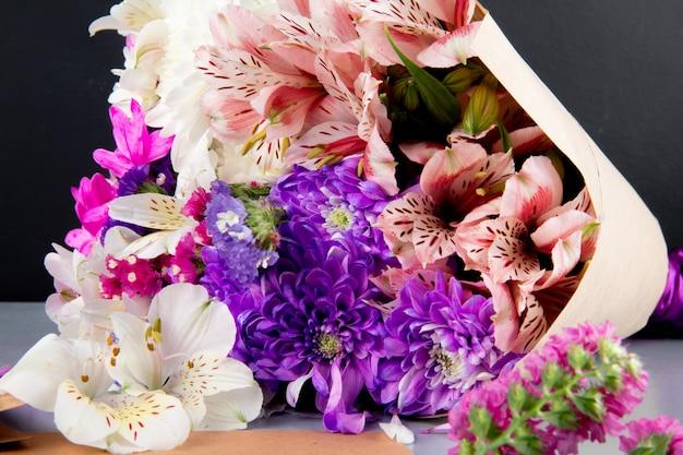 Вид сверху на букет из белых и розовых цветов альстромерии и хризантемы в крафт-бумаге на темном фоне