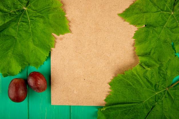 Вид сверху лист коричневой бумаги со сладким виноградом и зелеными листьями винограда на зеленом деревянном столе