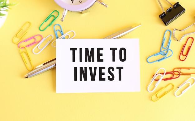 黄色の背景に「投資する時間」というテキストが付いた名刺の上面図。