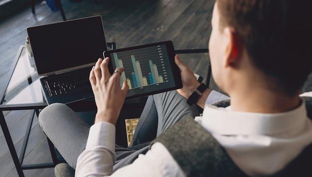 Вид сверху деловой человек, держащий планшет с графикой, сидя в своем офисе.