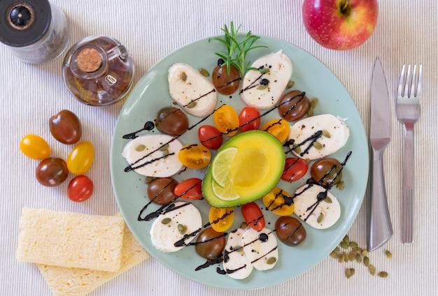 カプレーゼサラダの上面図。チーズモッツァレラチーズと小さなトマト、コショウ、バルサミコ酢のプレート。健康的で菜食主義の食事を補完するための半分のアボカドとリンゴ