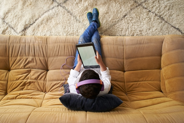 自宅のソファに座ってタブレットで遊んでヘルメットを持つ白人の少年の上面図