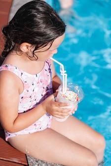 Вид сверху на ребенка в розовом купальнике, пьющего коктейль и сидящего на краю бассейна в ...
