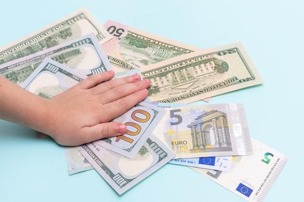 Вид сверху на руку ребенка за деньги, доллары и евро