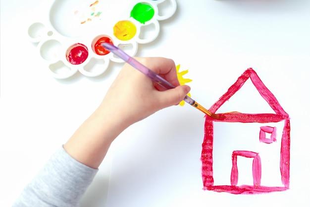 Вид сверху руки ребенка с кистью рисует картину загородного дома акварелью на белой бумаге. вид сбоку.