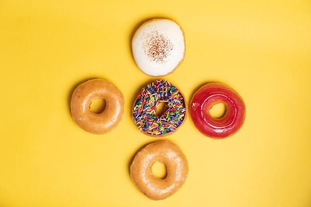 振りかけるチョコレートつや消しドーナツ、砂糖艶をかけたフロスト、イチゴ艶をかけられ、黄色の表面にバイエルンドーナツの平面図