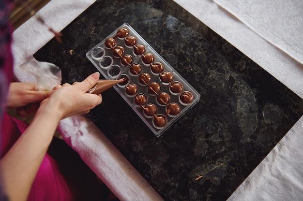 キャンディーバッグを保持し、液体の温かいチョコレートの塊をキャンディーの型に押し込むショコラティエの上面図。手作りの贅沢なチョコレートを作るプロセス。 Premium写真