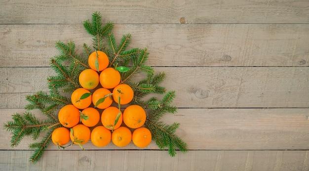コピースペースと暗い木製の背景に新鮮なオレンジと枝の木から作られたクリスマスツリーの上面図。休日のための代替のクリスマスツリーまたはポストカードのアイデア