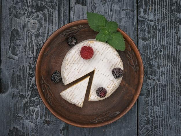 Вид сверху глиняной миски с сыром камамбер на черном деревянном столе. продукт из натурального молока.