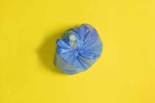 黄色の背景に閉じた青いゴミ袋のトップビュー