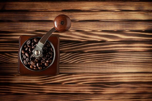 木製のテーブルにコーヒー豆とコーヒーグラインダーの上面図