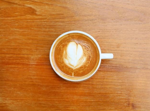 木製の背景に白い杯のハート型のコーヒーのトップビュー