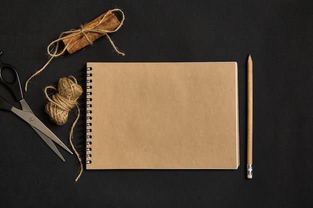 コピースペース、木製の鉛筆、ロープで結ばれたシナモンと黒い背景の上に横たわってはさみと空の空白の紙シートとクラフトメモ帳の上面図