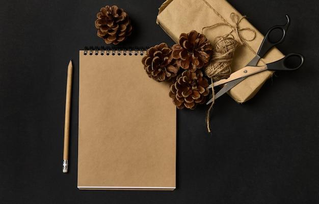 ロープで結ばれたシナモンで飾られた茶色の包装紙のクリスマスプレゼントの横にある黒い背景に白紙のシート、木製の鉛筆、はさみ、松ぼっくりのクラフトメモ帳の上面図