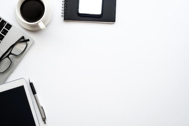 スマートフォンとコーヒータブレットを置いたクリエイティブなワークスペースの上面図。デスクホワイト