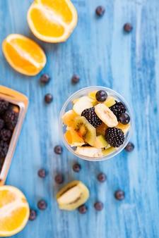 カップにおいしい果物がいっぱい入ったカップの上面図。ベリー、木製のテーブルにバナナオレンジ