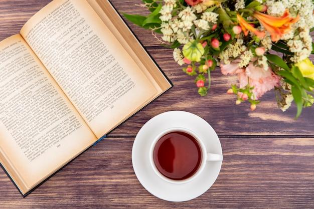 木材にカラフルで別の花と紅茶のカップのトップビュー