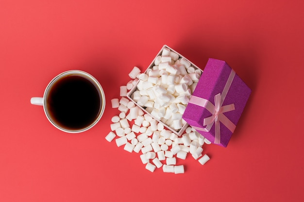 Вид сверху на чашку кофе и коробку с зефиром. сладкое угощение. плоская планировка.