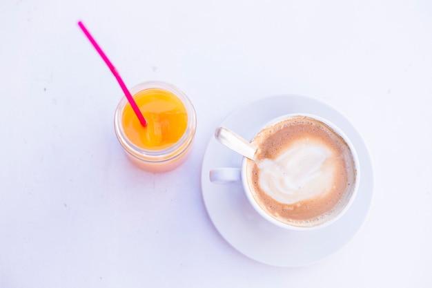 テーブルの上のコーヒーとオレンジジュースのカップの平面図です。昼間、ライフスタイル