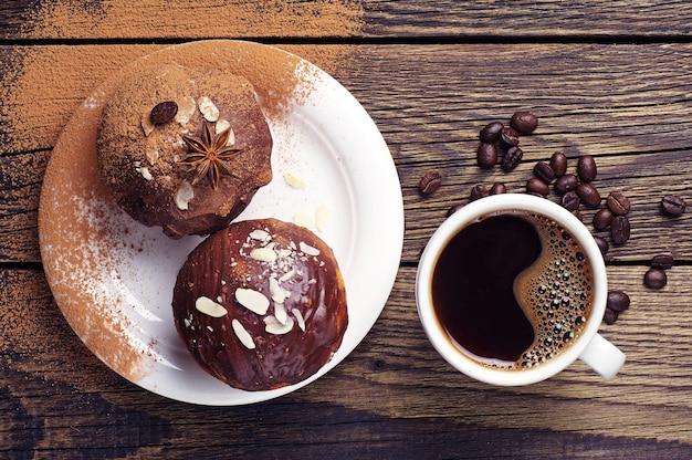 木製のテーブルにチョコレートとナッツとコーヒーとカップケーキの上面図