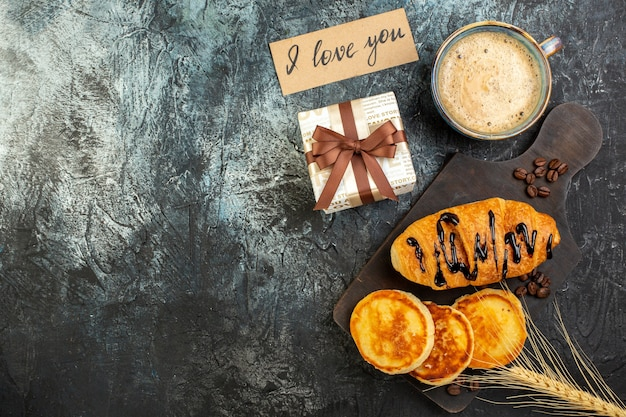 Вид сверху на чашку кофе и свежий вкусный завтрак, красивая подарочная коробка, блины круазан на темном фоне
