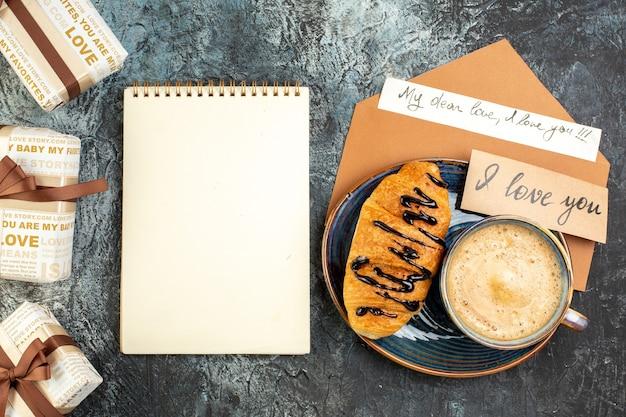 Вид сверху на чашку кофе и свежий вкусный круазан, красивые подарочные коробки для любимого человека и спиральный блокнот на темной поверхности