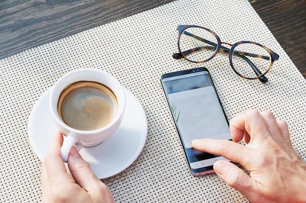 電話でメッセージを入力しているコーヒーグラスと手のカップの上面図。