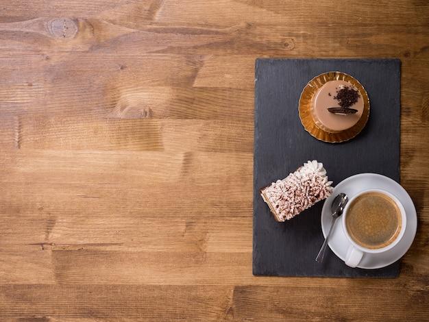나무 탁자에 있는 두 개의 다른 초콜릿 케이크 근처에 있는 커피 한 잔의 최고 전망. 맛있는 사막. 맛있는 케이크. 신선한 케이크. 복사 공간이 있습니다.