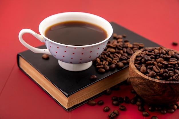 빨간색 배경에 고립 된 원두 커피와 커피 한 잔의 상위 뷰