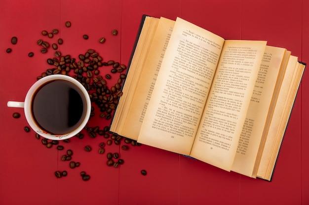 赤の背景に分離されたコーヒー豆とコーヒーのカップの上から見る