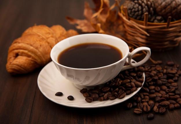 Вид сверху на чашку кофе с кофейными зернами, изолированную на деревянной поверхности
