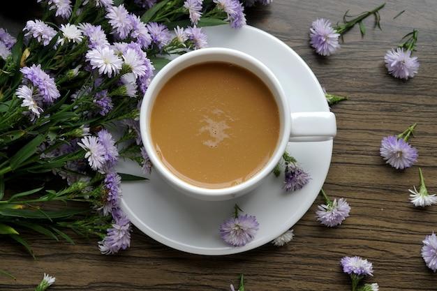 木製の背景に紫のマーガレットの花とホットコーヒーのカップの上面図