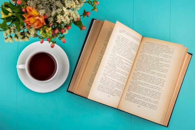 青の葉と美しい花とお茶のカップのトップビュー