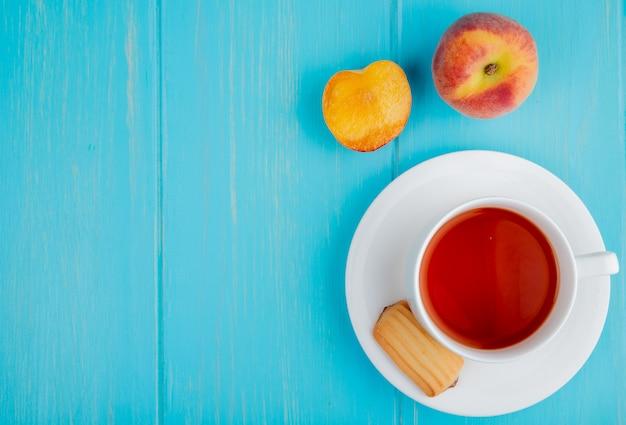 Вид сверху на чашку чая с печеньем и свежие спелые персики на синем с копией пространства