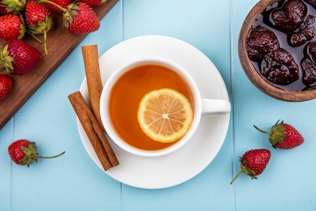 青色の背景に木製のボウルにいちごジャムとシナモンスティックのお茶のトップビュー