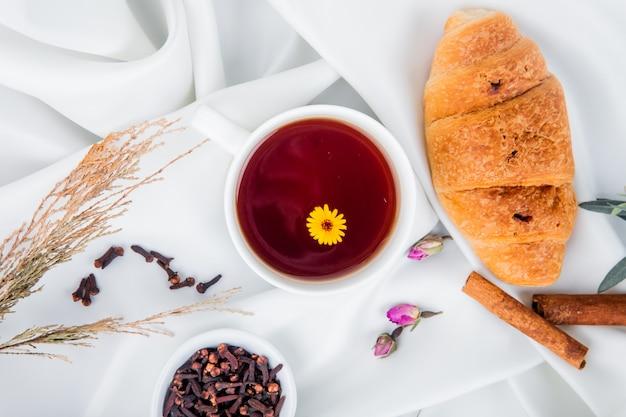 Вид сверху на чашку чая с круассаном и палочки корицы и гвоздики специи на белом