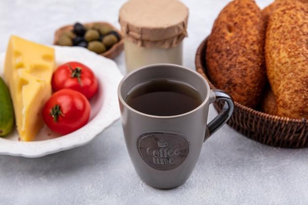 흰색 배경에 그릇에 야채와 함께 양동이에 신선한 빵과 차 한 잔의 상위 뷰