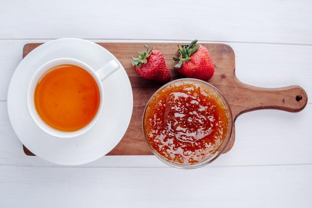 Вид сверху на чашку чая со свежей спелой клубникой и вареньем в миску на деревянной разделочной доске на белом