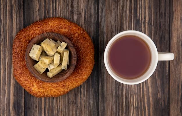 木製の背景にチーズの刻んだスライスと木製のボウルの上に新鮮なトルコのベーグルとお茶の上面図