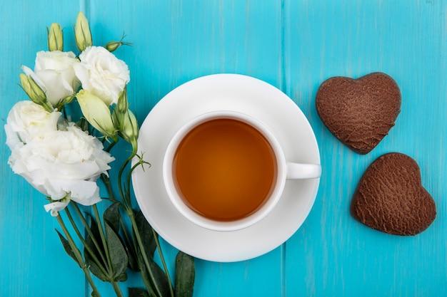 青い木製の背景に美しい白いバラとハート型のクッキーとお茶の上面図