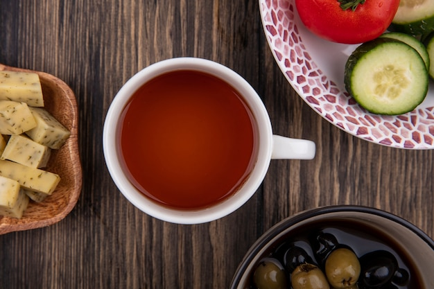 Вид сверху на чашку чая с оливками, овощами и нарезанными ломтиками сыра на деревянном фоне
