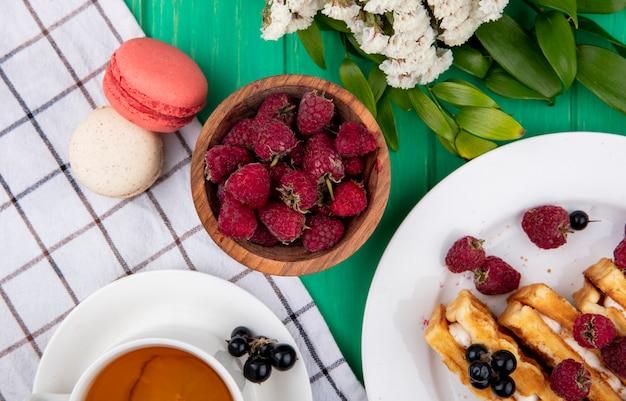 Вид сверху на чашку чая с малиной, вафлями, макаронами и цветами на клетчатом полотенце