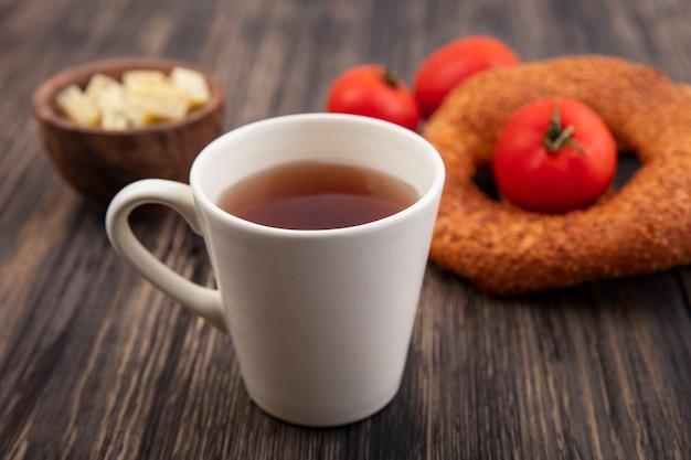 Вид сверху на чашку чая с турецкими бубликами и свежими красными помидорами, изолированными на деревянном фоне