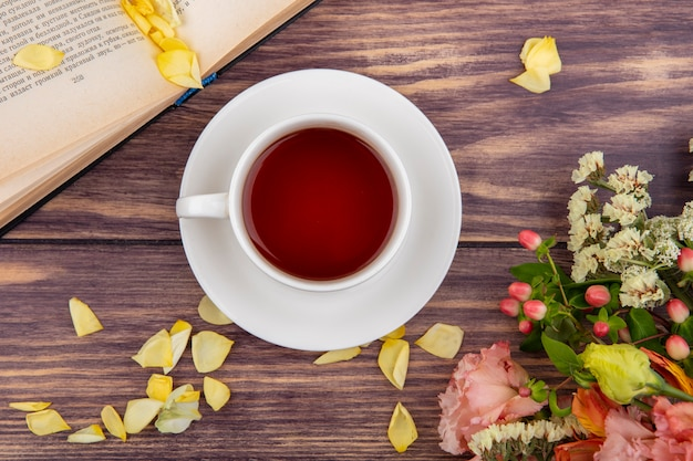 Вид сверху на чашку чая с желтыми лепестками цветов на дереве